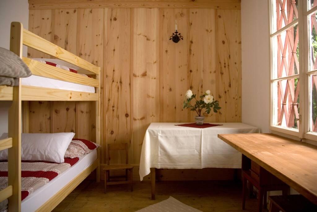 Kinderzimmer mit Stockbetten und Holzofen