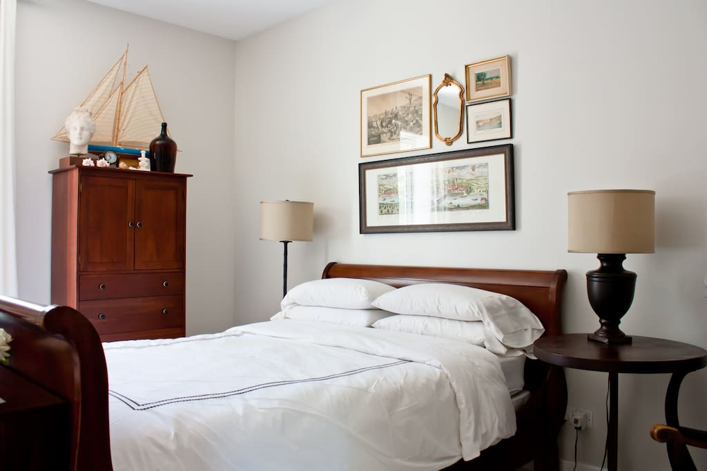 The queen-size bed features a firm mattress and plenty of pillows. Guests can use the cabinet to store their belongings, instead of living out of a suitcase.