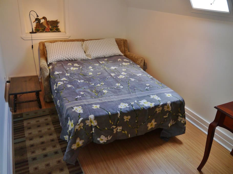 The 'Spare Room' in bed mode. It has a pull-out sofa double bed with extra padding, and a desk. Guest groups of two or more may use it. For example,  two guests may sleep in separate beds.