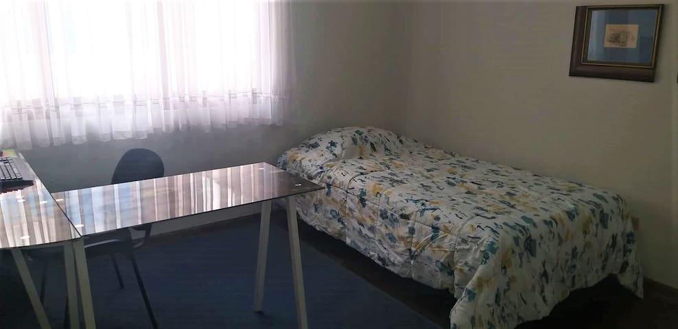 Dormitorio para una persona con computadora