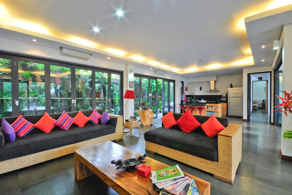Living room and kitchen area, full of daylight and fresh air through surrounding sliding doors.