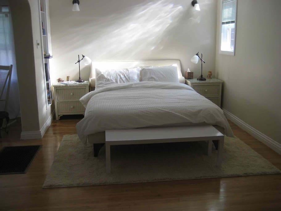 Bedroom features wall sconces with dimmer, glass block skylight, custom recessed bookshelf, wicker nighttables, west-facing window.
