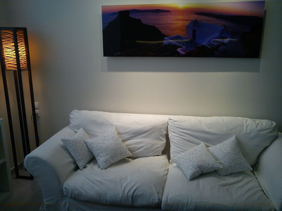 The printed photograph of Santorini above the couch reminds one of the greek paradise islands