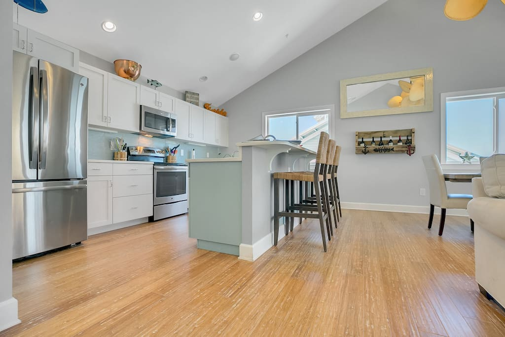 Open kitchen space with French-door refrigerator and a starter supply of dish soap and paper towels.