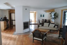 A large dining/living room/kitchen area surrounds a European-style masonry heater and bakeoven.