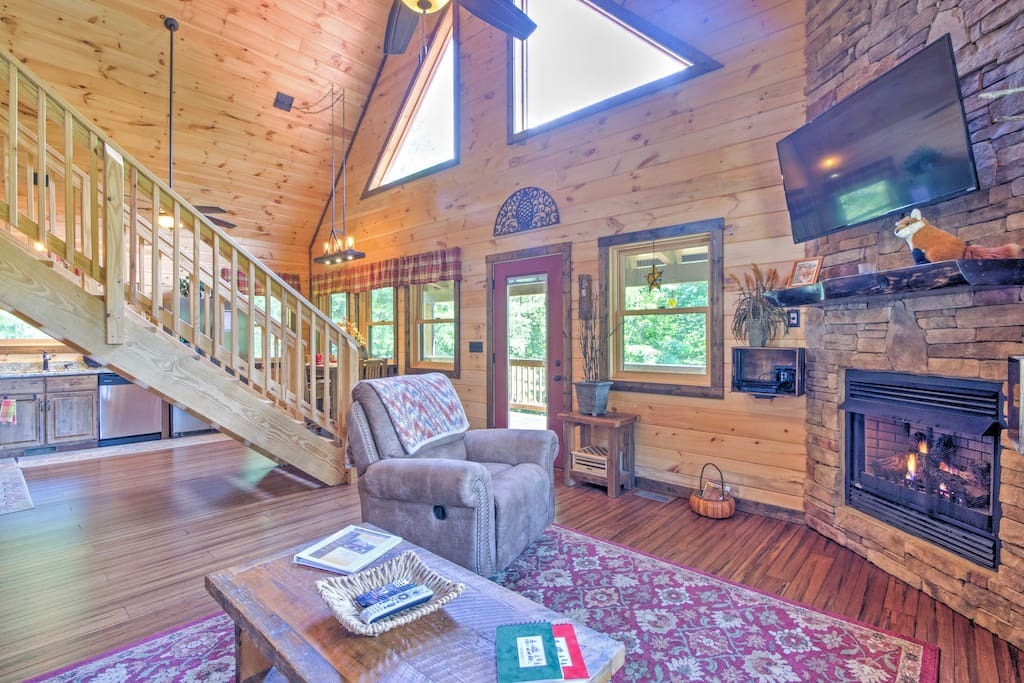 This beautiful cabin offers rustic wood paneling, large windows, vaulted ceilings, and a wood-burning fireplace.