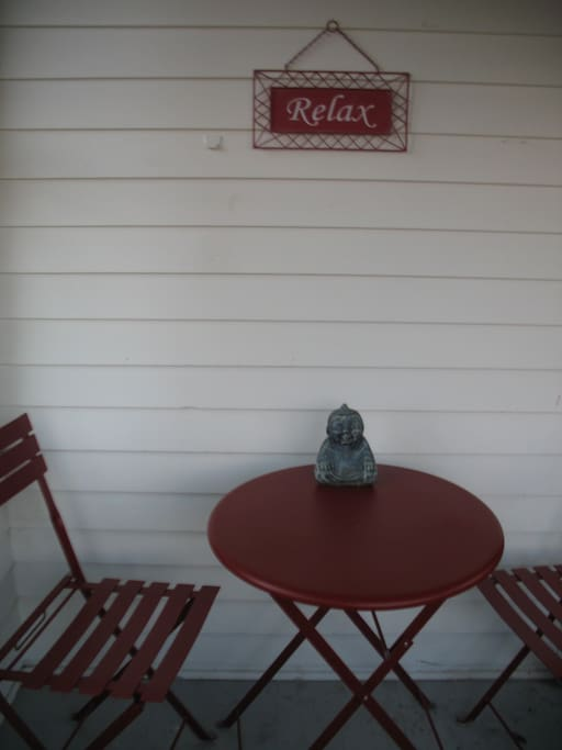 The table and chairs on the enclosed front porch, with our motto:  Relax.  :)