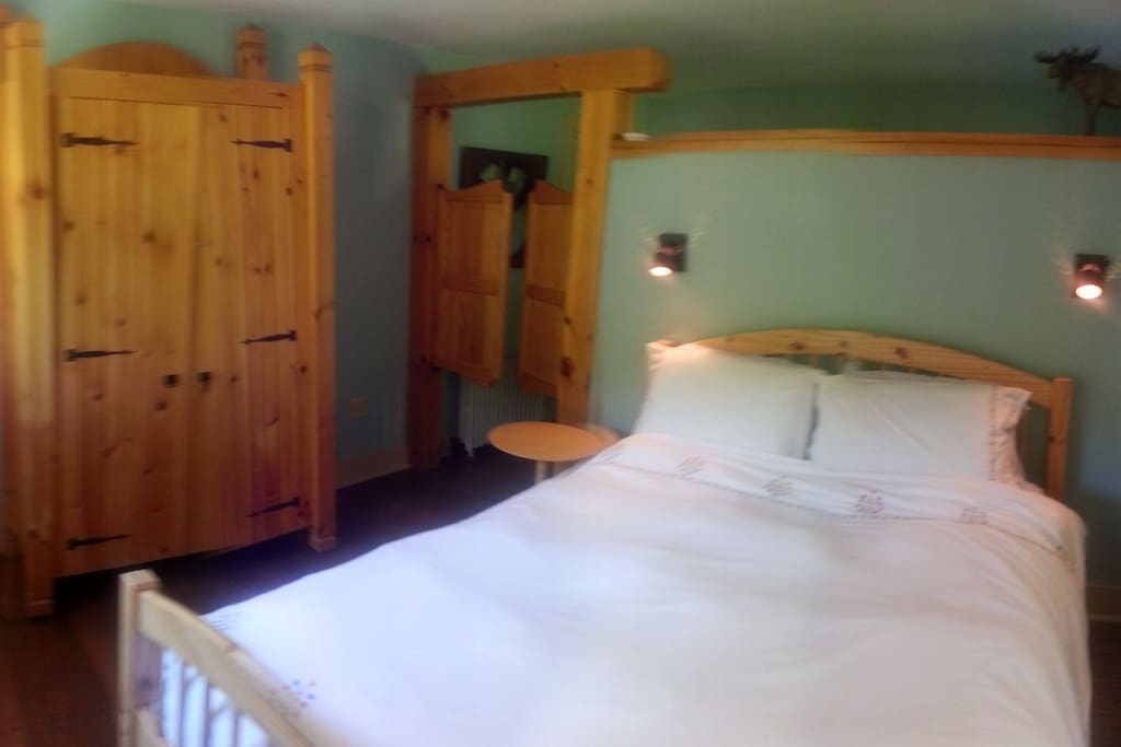 Suite Bedroom. Luxurious bedding and wood accents throughout.