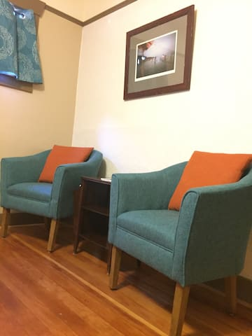 Sitting area in your bedroom. Room has a closet, 2 suitcase stands, and is stocked with towels and emergency supplies.