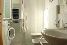 Il bagno è spazioso, luminoso e con finestra, doccia e lavatrice Bathroom is spacious and bright with window, shower and washing machine