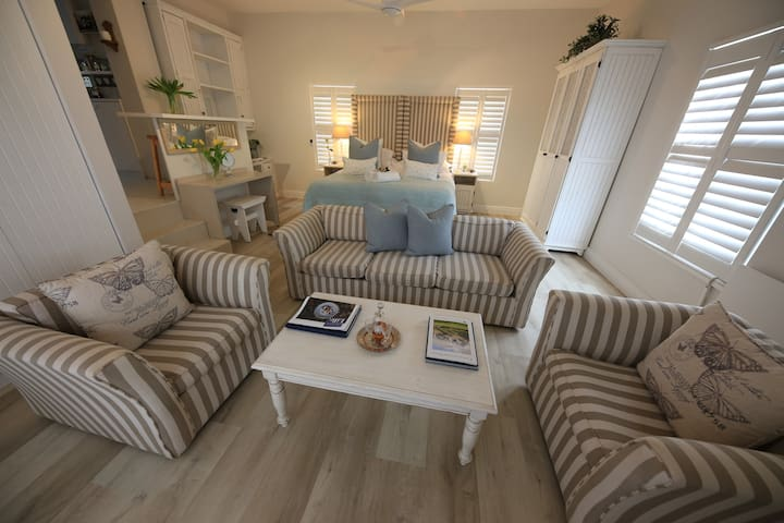 Deluxe Garden suite with own lounge area, kitchenette, ensuite shower and doors to private garden patio