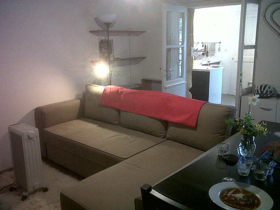 Lounge with comfortable sofa adjacent to kitchen.