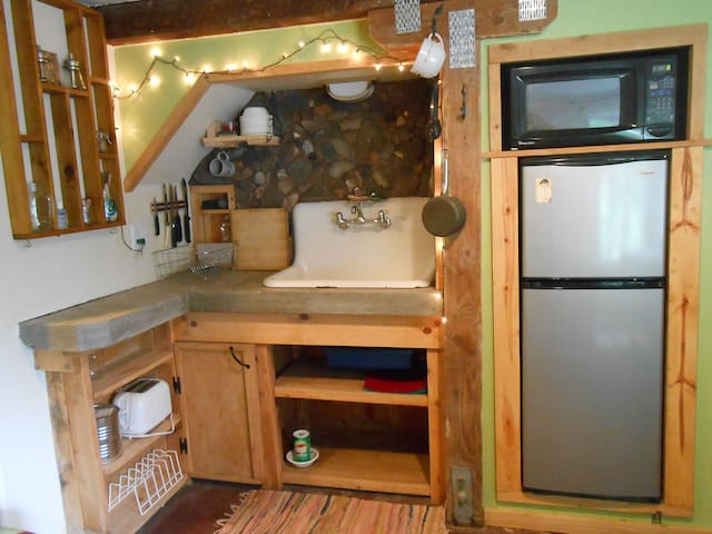 kitchenette with sink, refrigerator, freezer, microwave, dishes and utensils.