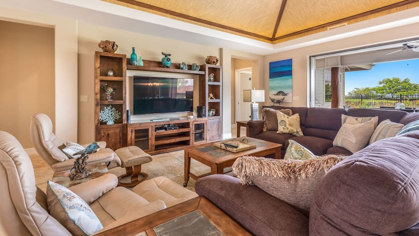 Spacious living area with high-end lounge chairs, plush sofas, and large flat-screen TV.