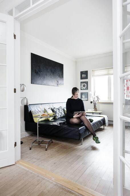 Skøn lys stue med stor sofa som man nemt kan sove 2 personer på.