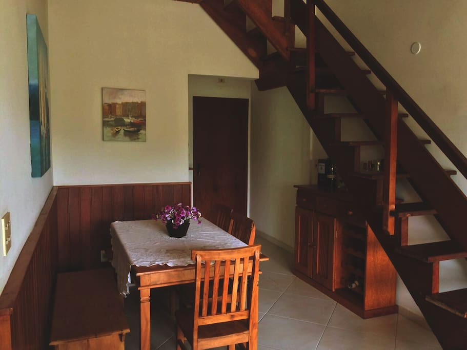 Mesa com 6 lugares, hall de entrada, escada para segundo andar onde temos a area externa