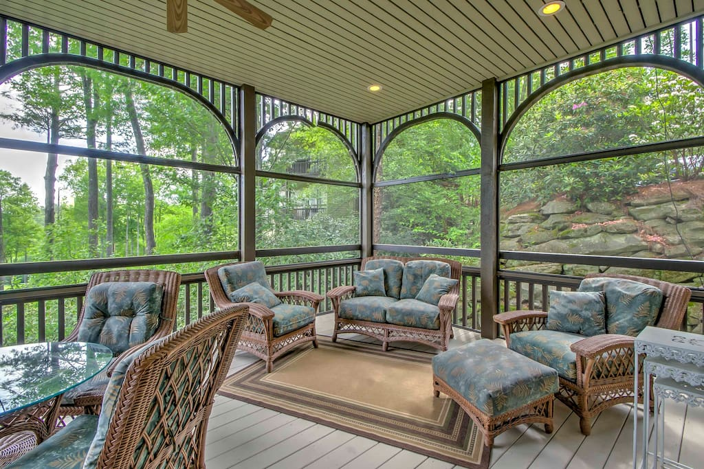 The condo features a spacious screened-in porch with plenty of comfortable furniture.
