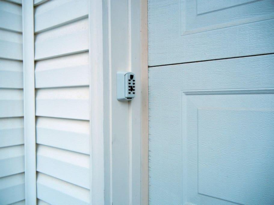 Lockbox with key on front door frame of garage