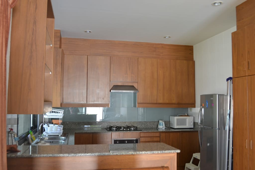 Western kitchen with gas burner, oven, coffee maker,microwave oven, toaster and clothes washing machine.
