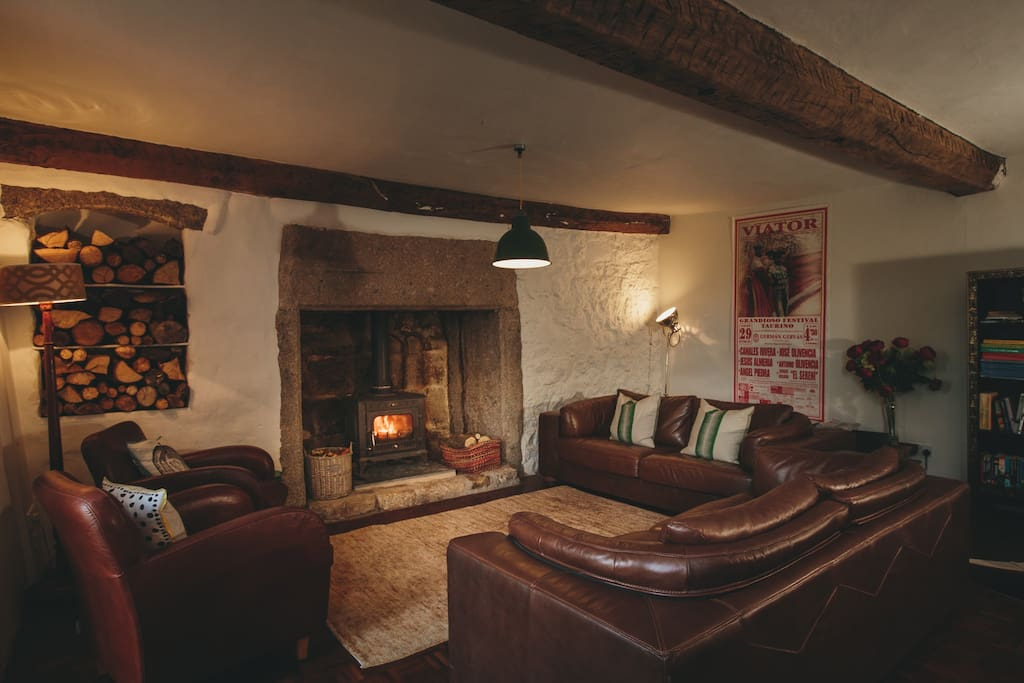 Large lounge with leather sofas and wood burning stove