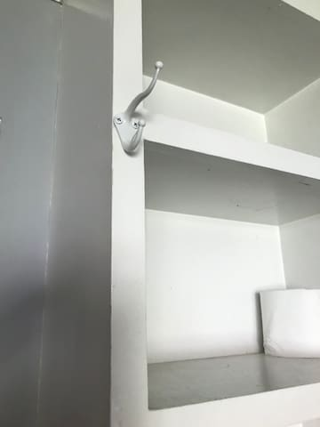 There are 2 double hooks for hangers or clothes. Hangers are also provided (look inside in a cabinet).