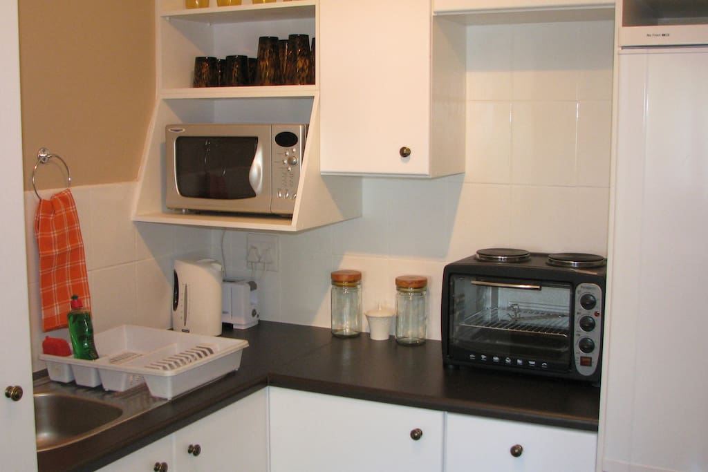 Fully equipped self catering kitchen with full size fridge, microwave, kettle, toaster, 2 plate hob with stove.