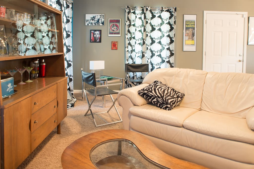 LIving room is decorated with original art works and mid-century modern furniture.