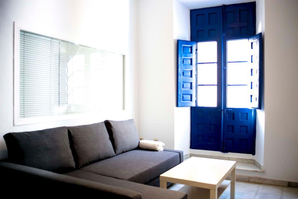 Salón. Sofá cama, balcón y ventanal de iluminación hacia el dormitorio.