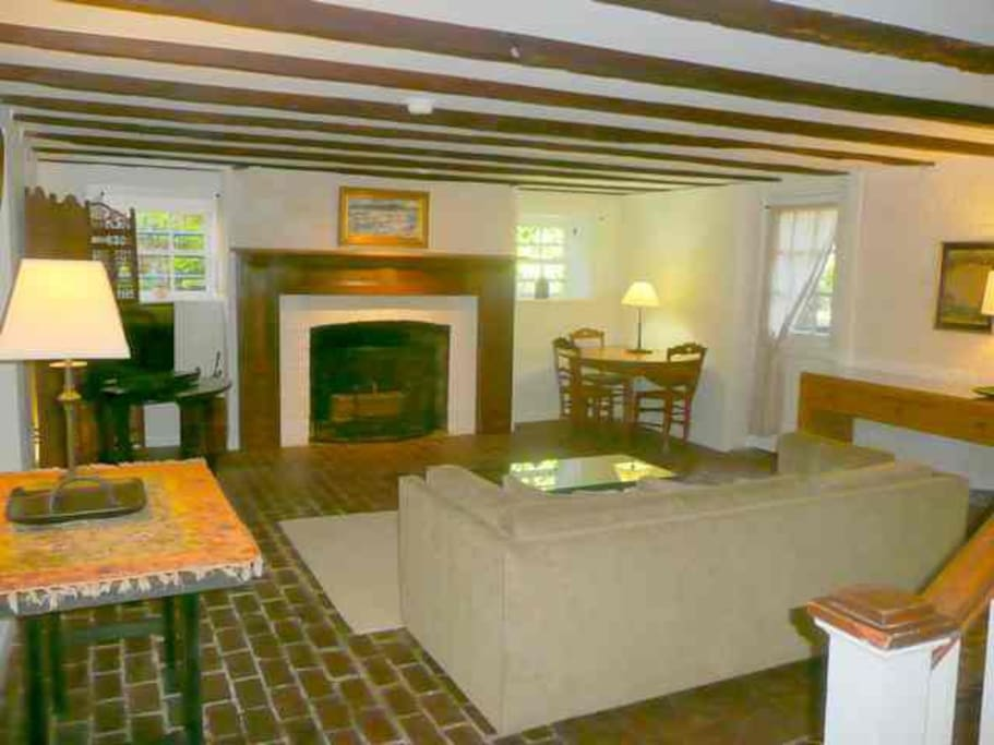 Large living room with working wood fireplace, lots of windows and historic wood beam ceiling.