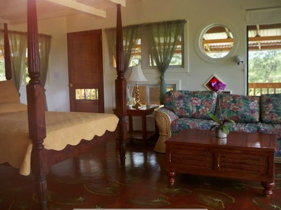 The bedroom on the second floor has beautiful, comfortable furniture, and tropical views in all directions.