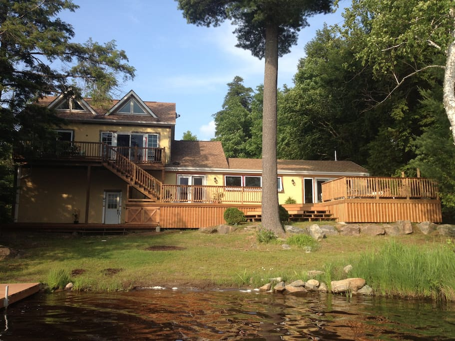 View from the lake.  Fire pit, 1000 sq ft deck, SW facing with nightly sunset, outdoor hot tub
