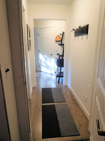 Welcome!  A well lit hallway to bedroom with coat rack & mirror.