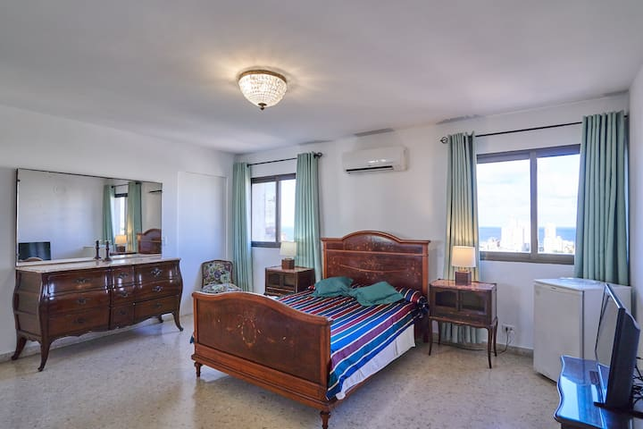 Confortable Room in the 14th floor decorated with a modern style with 20m2. Includes a 2x2 bed.  a private bathroom ,cold and hot water 24/7, soap, hair dryer .  a mini fridge, safe box,  TV , air conditioner,  an amazing view of the city ad the sea.