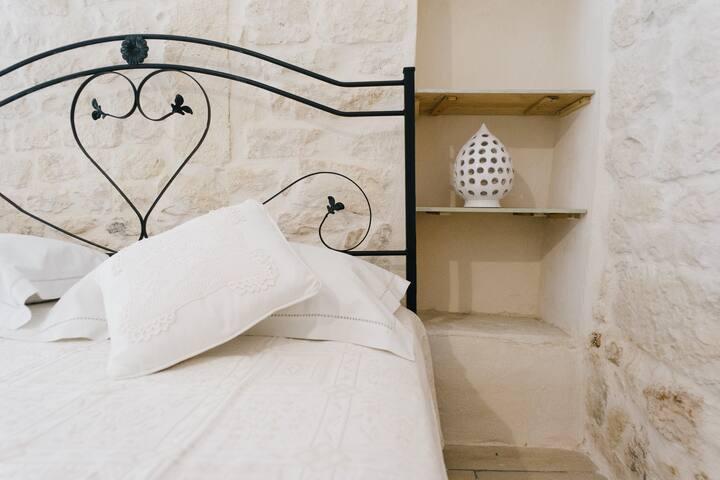Dettaglio del letto con abat-jour in ceramica di Grottaglie (lato sinistro)
