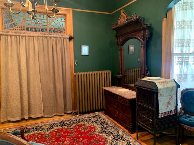 Located on the main floor of the house is the master bedroom. A full size loveseat located at the foot of the bed.  Beautifully furnished with Victorian era furniture.