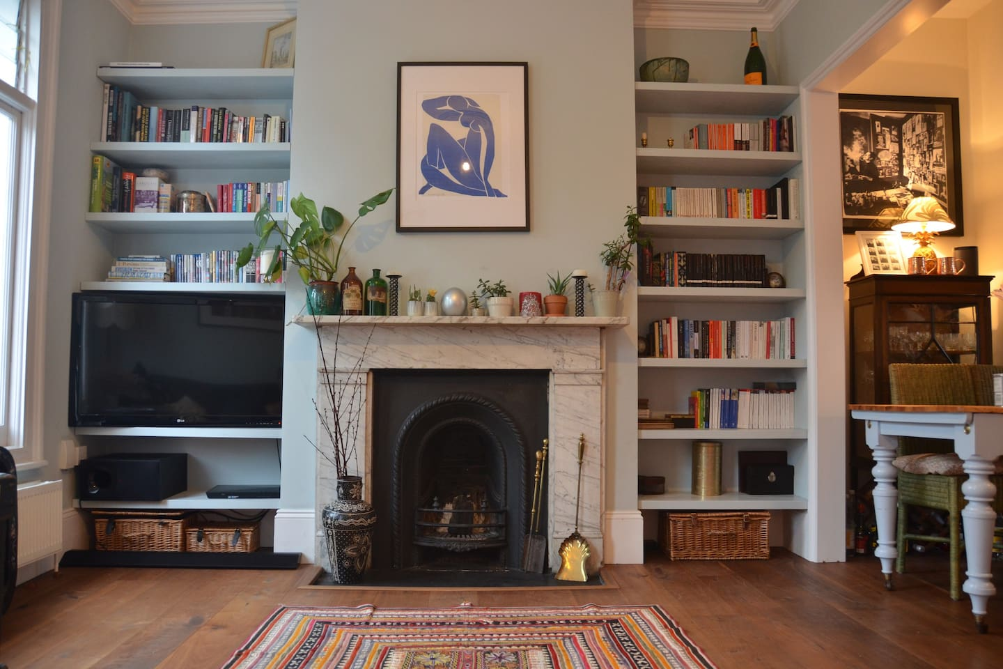 The living room, with original fireplace, TV (with Amazon Firestick / Netflix etc) and Victorian fireplace