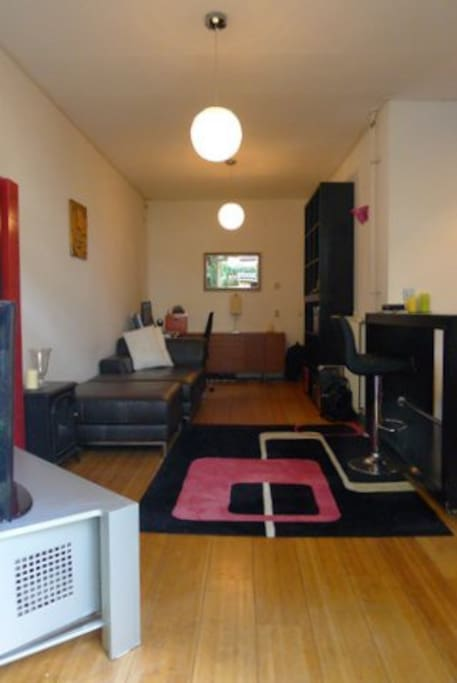 leather coach, flat screen tv,  a work station and kitchen