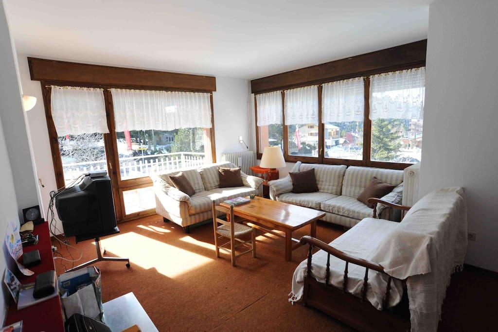 Salon avec accès à la terrasse équipé de trois canapé dont un convertible en lit double
