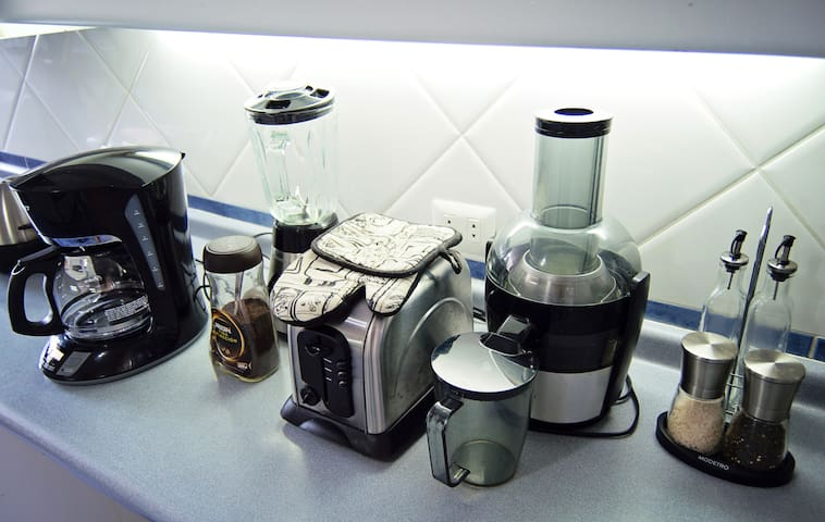 Kitchen, with juicer, blender, toaster, sandwich maker and free coffee.
