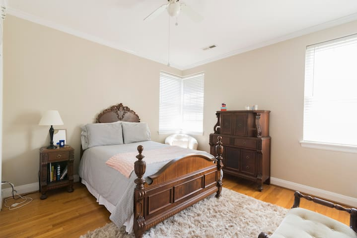 Guest bedroom with full bed, vanity for getting ready in natural lighting.