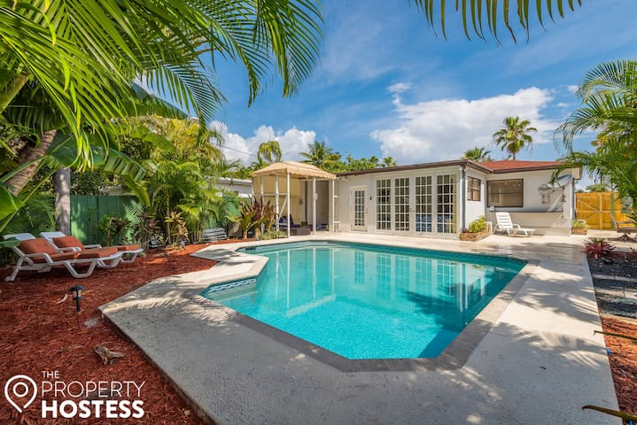 Gorgeous and bright backyard, fully equipped with lounge chairs, a ready-to-use BBQ grill, and a full seating table