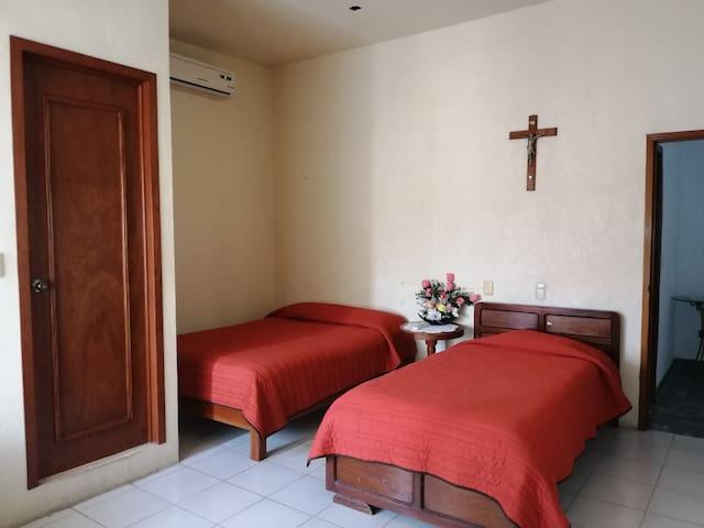 Habitación con una Cama matrimonial y dos camas individuales, aire acondicionado, closet, baño privado con agua caliente, silla, alta para bebé.