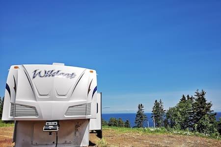 Camping car en montagne avec vue sur la mer.