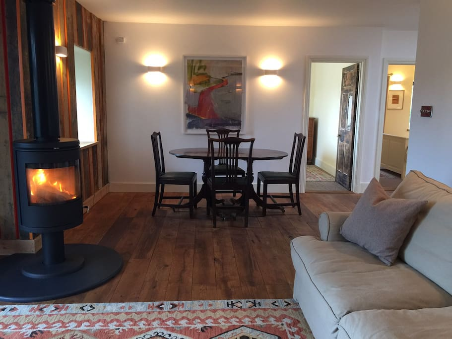 Open plan living / dining room with freestanding Morso wood fire