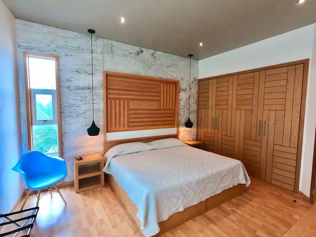 Habitación principal con una cama king size, clóset con perchas, aire acondicionado y televisión con pantalla curva, entre otros