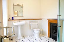 Nelson's suite bathroom with victorian style shower and original fireplace.  Please contact us if you would be interested in booking this room as part of your visit.