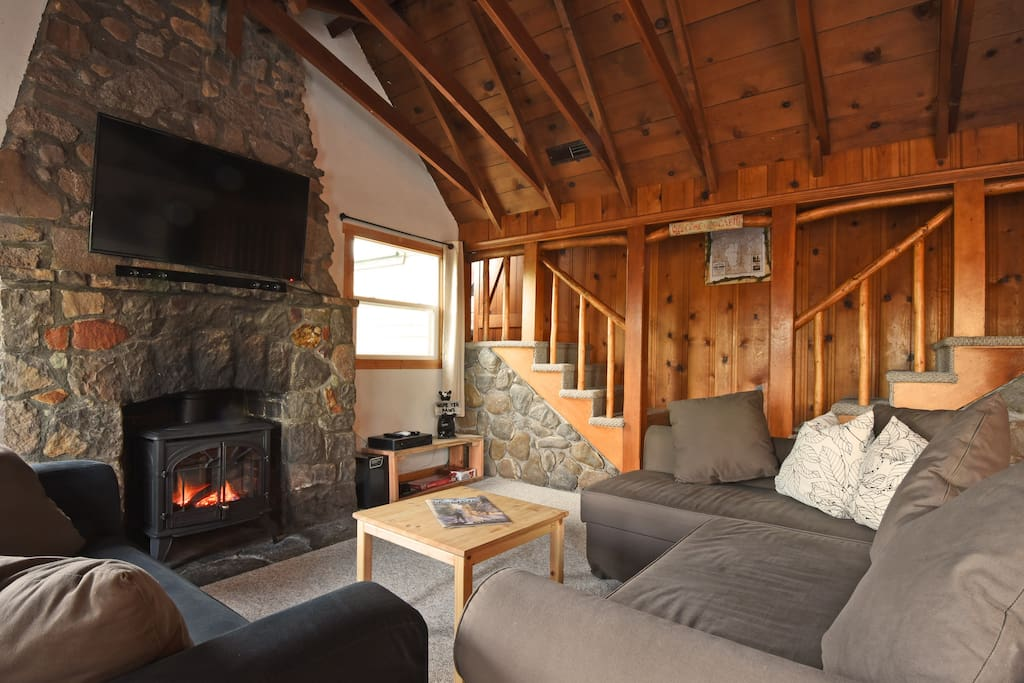The living room, featuring the TV and a wood burning stove