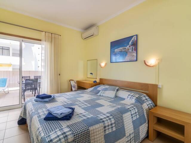 Ruime slaapkamer. 2 persoons bed (180x200), inbouwkast, buro, via schuifpui toegang tot terras, airco.