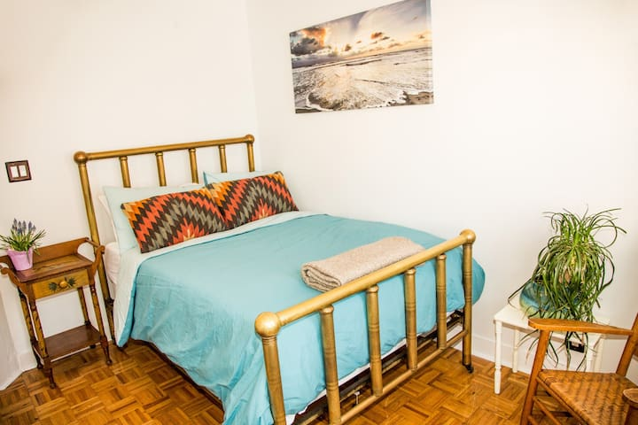This bright bedroom has a double brass bed with a new memory-foam mattress.