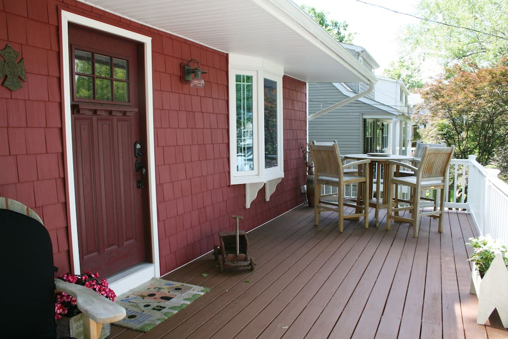Spacious front porch with 2 adirondack chairs and seating for 4.